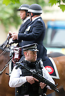 Armed Police officers arrive at the junction of the Mall and Horse Guards Road for the Royal Wedding in London Friday, April, 29, 2011. (AP Photo/Bogdan Maran)