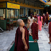May 09, 2013 - Yangon, Myanmar: A Buddhist novice uses his mobile phone to take photographs of a shrine at Sule Pagoda in central Yangon. CREDIT: Paulo Nunes dos Santos