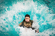 Victor Company cadet Kevin Pham jumps into the water with his rifle during Palmetto Battalion Army ROTC's combat water survival test at The Citadel in Charleston, South Carolina on Thursday, April 1, 2021. Credit: Cameron Pollack / The Citadel