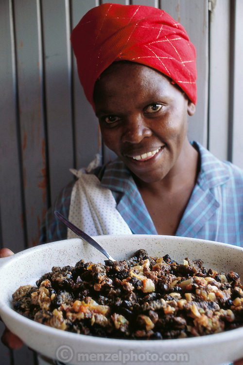 Catherine Lemekwana with a mopane worm stew she prepared for her family using dried mopane worms, onions, garlic, salt, and curry in her home in Soweto, (South West Township), Johannesberg, South Africa. The harvest of mopane worms is a major economic event in Botswana where whole families move into the countryside and set up camp in order to collect the worms. Dried mopane worms have three times the protein content of beef and can be stored for many months. Image from the book project Man Eating Bugs: The Art and Science of Eating Insects.