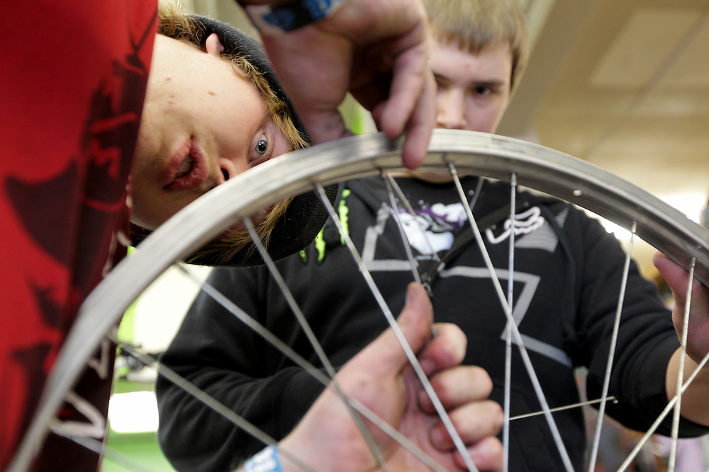 Ty Spangle, 17, left, shows apprentice Marcus Wachholz, 17, how to replace a spoke on a refurbished bicycle at Express Bike Shop in St. Paul, Minnesota.  Formerly a Youth Express apprentice, Spangle is now a mechanic at the shop, teaching skills to new program participants..