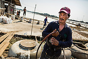 "28 MARCH 2014 - NA KHOK, SAMUT SAKHON, THAILAND: A Thai worker cools off with tap water on a salt farm in Samut Sakhon province. Thai salt farmers south of Bangkok are experiencing a better than usual year this year because of the drought gripping Thailand. Some salt farmers say they could get an extra month of salt collection out of their fields because it has rained so little through the current dry season. Salt is normally collected from late February through May. Fields are flooded with sea water and salt is collected as the water evaporates. Last year, the salt season was shortened by more than a month because of unseasonable rains. The Thai government has warned farmers and consumers that 2014 may be a record dry year because an expected ""El Nino"" weather pattern will block rain in mainland Southeast Asia. Salt has traditionally been harvested in tidal basins along the coast southwest of Bangkok but industrial development in the area has reduced the amount of land available for commercial salt production and now salt is mainly harvested in a small parts of Samut Songkhram and Samut Sakhon provinces.    PHOTO BY JACK KURTZ"