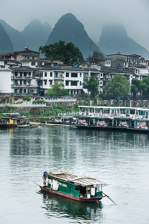 A boat crosses the Lijiang River on a foggy day in Yangshuo, China.