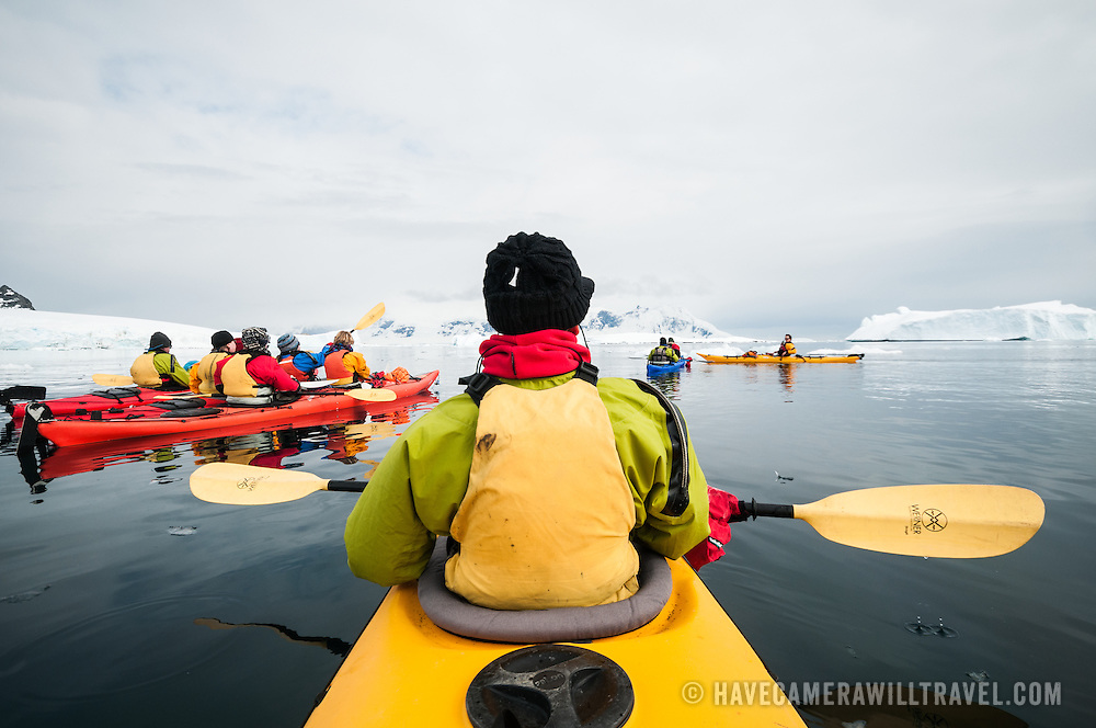 A point of view shot of kayaking in a tandem kayak gliding through still waters and icebergs at Cuverville Island on the Antarctic Peninsula.