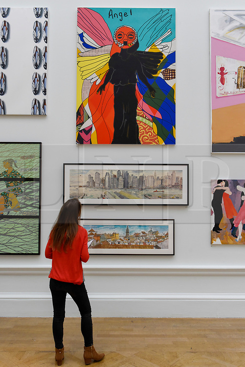 """© Licensed to London News Pictures. 08/06/2017. London, UK. A visitor views (top) """"Angel (Turquoise)"""" by Yinka Shonibare RA.  Preview of the Summer Exhibition 2017 at the Royal Academy of Arts in Piccadilly.  Co-ordinated by Royal Academician Eileen Cooper, the 249th Summer Exhibition is the world's largest open submission exhibition with around 1,100 works on display by high profile and up and coming artists.<br />  Photo credit : Stephen Chung/LNP"""