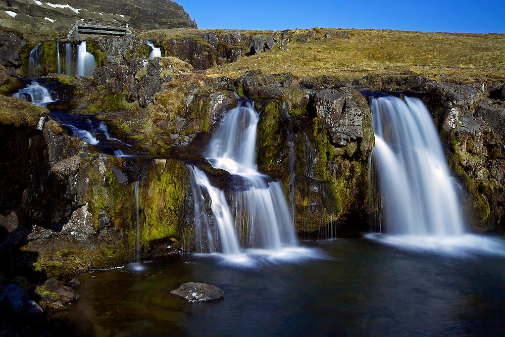 """Kirkjufellsfoss, which translates to """"Church Mountain Falls,"""" is a short but very well-situated waterfall near the distinctive Kirkjufell mountain in Grundarfjörður on the north side of the Snæfellsnes Peninsula in Iceland."""