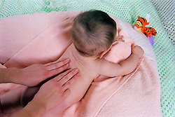 Young baby having body massage,