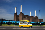 A yellow ice cream van passes Battersea Power Station in South London. This classic Art Deco brick design with it's distinctive four white towers is one of London's most famous landmarks. Now derelict and with plans for possible development, it remains one of the iconic designs which towers over the River Thames.