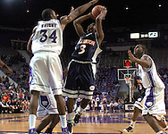 Cal State Fullerton guard Bobby Brown (3) puts up a shot under pressure from Kansas State's Akeem Wright (34) during the first half at Bramlage Coliseum in Manhattan, Kansas, November 30, 2005.  K-State beat Titans of Cal State Fullerton 84-59.