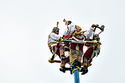 A Voladores position themselves at the top of a thirty-meter pole to perform the sacred ceremonial dance in the Parque Takilhsukut at the pre-Columbian archeological complex of El Tajin in Tajin, Veracruz, Mexico. The Danza de los Voladores is a indigenous Totonac ceremony involving five participants who climb a thirty-meter pole. Four of these tie ropes around their waists and wind the other end around the top of the pole in order to descend to the ground. The fifth participant stays at the top of the pole, playing a flute and a small drum. The ceremony has been inscribed as a Masterpiece of the Oral and Intangible Heritage of Humanity by UNESCO.