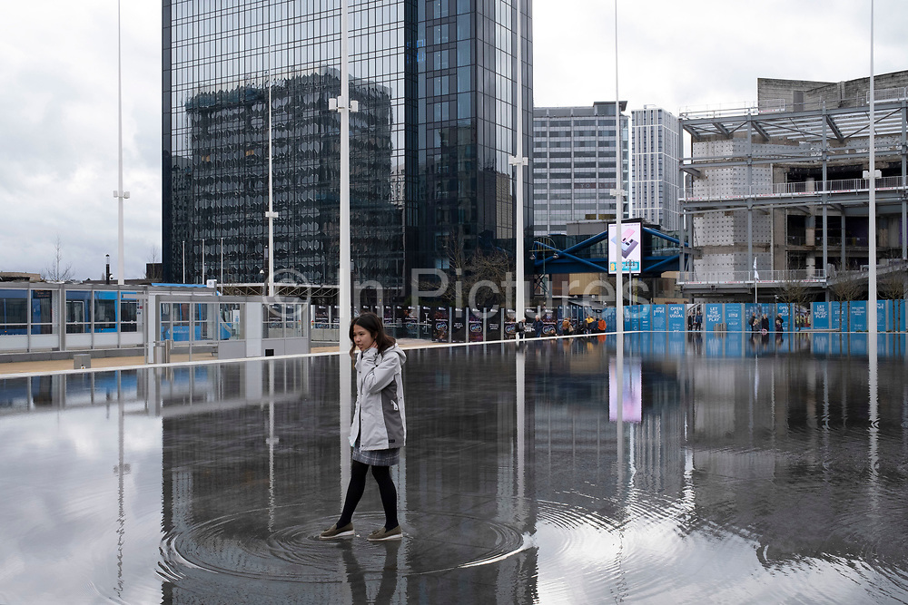 Woman standing in the fountains in Centenary Square on 14th March 2020 in Birmingham, United Kingdom. The £16m redevelopment of Birminghams Centenary Square has now been formally opened. Paradise, formerly named Paradise Circus, is the name given to an area of approximately 7 hectares in Birmingham city centre between Chamberlain and Centenary Squares. The area has been part of the civic centre of Birmingham since the 19th century. From 2015 Argent Group will redevelop the area into new mixed use buildings and public squares.