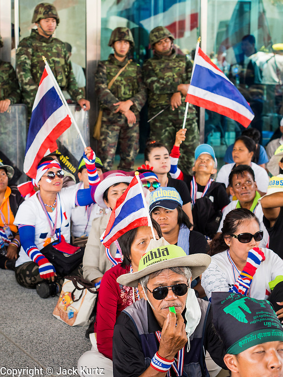 """08 APRIL 2014 - BANGKOK, THAILAND:  Anti-government protestors sitting in front of Thai soldiers block the entrance to the Ministry of Justice in Bangkok. Several hundred anti-government protestors led by Suthep Thaugsuban went to the Ministry of Justice in Bangkok Tuesday. Suthep and the protestors met with representatives of the Ministry of Justice and expressed their belief that Thai politics need to be reformed and that corruption needed to be """"seriously tackled."""" The protestors returned to their main protest site in Lumpini Park in central Bangkok after the meeting.    PHOTO BY JACK KURTZ"""