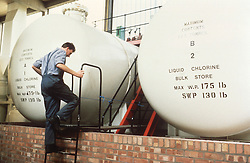 Man inspecting tanks at water treatment plant,