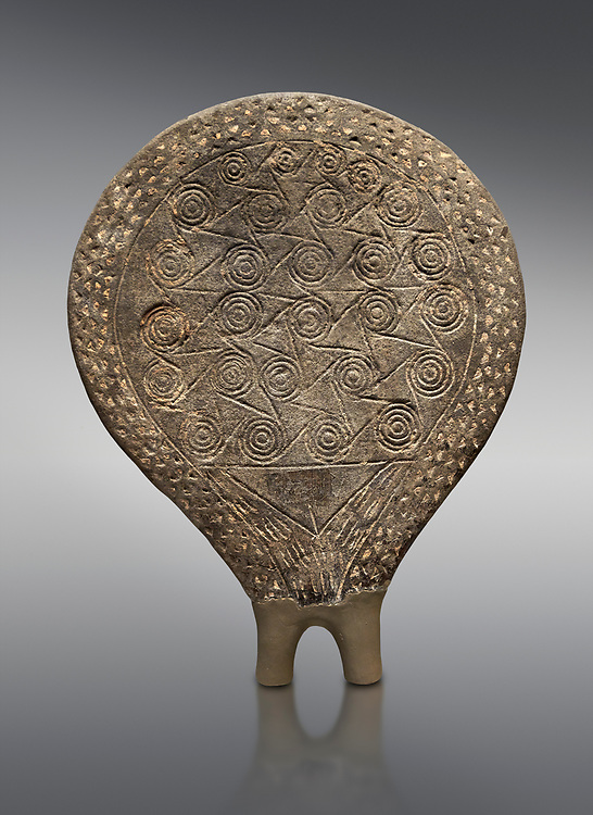 Cycladic terracotta 'frying pan' with incied decoration from  Syros. Early found  at Phylakopi, Melos. Cycladic period III 2300-2000 BC), National Archaeological Museum Athens, Cat No 6172.  Grey background.<br /> <br /> <br /> These so called 'frying pans' wre created by the Keros-Syros culture and are their useage is uncertain. The compex geometric patterns on their bases suggest that they may have had some symbolic meaning and were used in religious of magical rituals. They could also have served practical purposes being used as dishes, mirror mounts, astrolabes or metris measured for salt traders. .<br /> <br /> If you prefer to buy from our ALAMY PHOTO LIBRARY  Collection visit : https://www.alamy.com/portfolio/paul-williams-funkystock/cycladic-art-artefacts.html Type into the LOWER SEARCH WITHIN GALLERY box to refine search by adding background colour, place, museum etc<br /> <br /> Visit our CYCLADIC CIVILISATIONS PHOTO COLLECTIONS for more photos to download or buy as wall art prints https://funkystock.photoshelter.com/gallery-collection/Cycladic-civilisation-Ancient-Greek-Artefacts-art-Photos-Pictures-Images/C0000CmevVvnC.XU