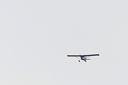 A small personal fixed wing aircraft with skis as landing gear flies in alignment to the Illinois River near Starved Rock State Park.