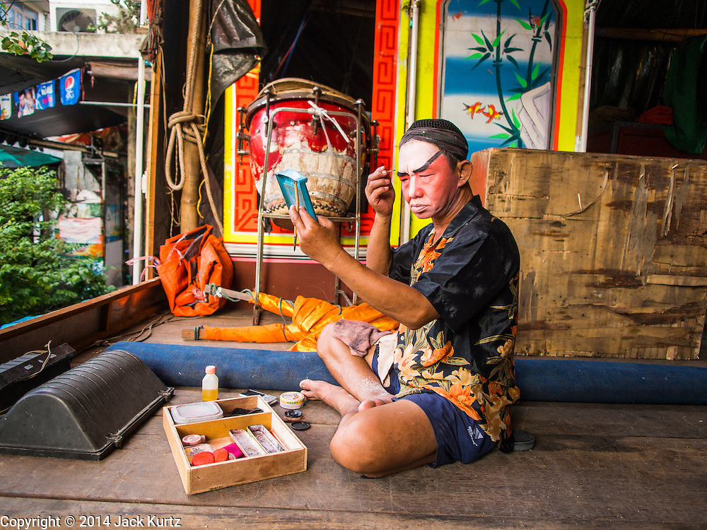 """18 AUGUST 2014 - BANGKOK, THAILAND: A member of the Lehigh Leng Kaitoung Opera troupe applies his makeup before a performance at Chaomae Thapthim Shrine, a small Chinese shrine in a working class neighborhood of Bangkok. The performance was for Ghost Month. Chinese opera was once very popular in Thailand, where it is called """"Ngiew."""" It is usually performed in the Teochew language. Millions of Chinese emigrated to Thailand (then Siam) in the 18th and 19th centuries and brought their culture with them. Recently the popularity of ngiew has faded as people turn to performances of opera on DVD or movies. There are still as many 30 Chinese opera troupes left in Bangkok and its environs. They are especially busy during Chinese New Year and Chinese holiday when they travel from Chinese temple to Chinese temple performing on stages they put up in streets near the temple, sometimes sleeping on hammocks they sling under their stage. Most of the Chinese operas from Bangkok travel to Malaysia for Ghost Month, leaving just a few to perform in Bangkok.     PHOTO BY JACK KURTZ"""