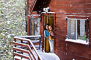 Three women smiling from cabin door in winter, San Bernardino National Forest, California USA