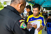"""Thai immigration police check the temporary ID cards of undocumented Cambodian workers at the temporary """"one stop service center"""" in the Bangkok Youth Center in central Bangkok. Thai immigration officials have opened several temporary """"one stop service centers"""" in Bangkok to register undocumented immigrants and issue them temporary ID cards and work permits. The temporary centers will be open until August 14."""