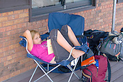 Teen girl resting and reading in canvas chair. Dragon Festival Lake Phalen Park St Paul Minnesota USA