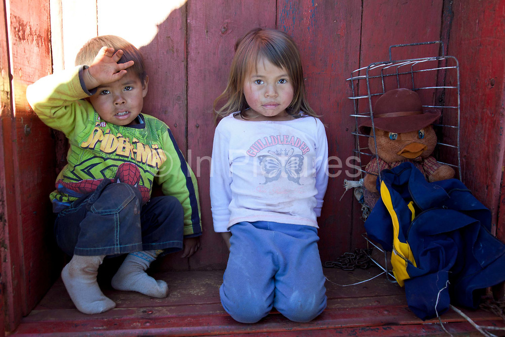 Guarani children looking at the camera and sitting down. The Guarani are one of the most populous indigenous populations in Brazil, but with the least amount of land. They mostly live in the State of Mato Grosso do Sul and Mato Grosso. Their tradtional way of life and ancestral land is increasingly at risk from large scale agribusiness and agriculture. There have been recorded cases and allegations of violence between owners of large farms and the Guarani communities in this region.