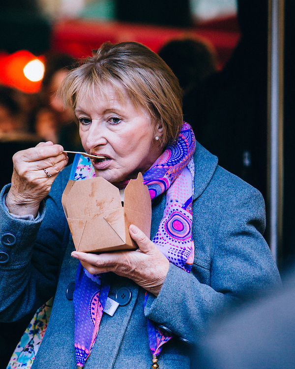 A woman eating from a paper box in a outdoor market