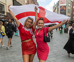 Licensed to London News Pictures. 07/07/2021. London, UK. England fans (L) Emily Merritt 19 and Abbey Kidd 21 from Dartford cheer and wave a flag in Leicester Square, London ahead of the Euro 2020 semi-final between England and Denmark at Wembley tonight for a place in the finals this Sunday (11 July 2021). Today, England taken on Denmark in the first semi-final since 1996 as eager fans start to gather in London. Photo credit: Alex Lentati/LNP