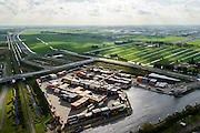 Nederland, Zuid-Holland, Alphen aan de Rijn, 23-10-2013; containeroverslagterminal, binnenvaartterminal gelegen aan rivier de Gouwe. Multimodaal knooppunt: spoor, wegvervoer, water. Naast het bedrijventerrein het Alphen-aquaduct N11 onder de Gouwe en de spoorlijn. <br /> Container terminal located near the River Gouda. Multimodal hub: rail, road, water. Aqueduct (river Gouwe) over the motorway in Alphen aan de Rijn.<br /> luchtfoto (toeslag op standaard tarieven);<br /> aerial photo (additional fee required);<br /> copyright foto/photo Siebe Swart.