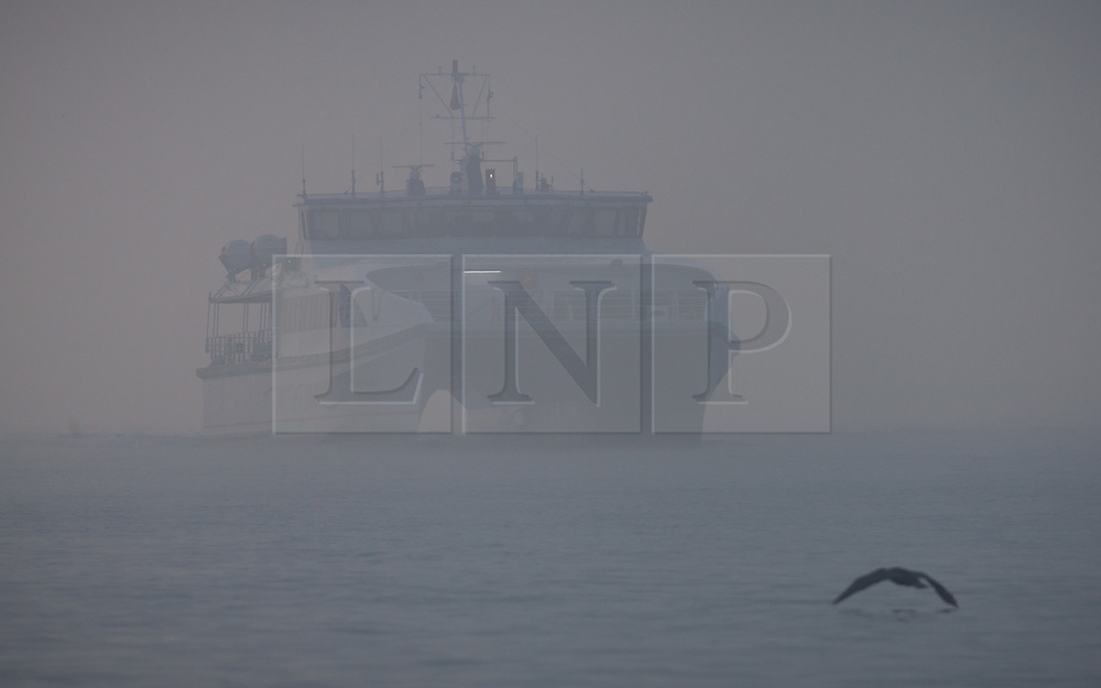 © Licensed to London News Pictures. 30/12/2016. Portsmouth, UK.  The Wightlink catamaran making its way into the foggy entrance of Portsmouth Harbour. People on the South Coast have woken up to foggy weather this morning, 30th December 2016. Photo credit: Rob Arnold/LNP