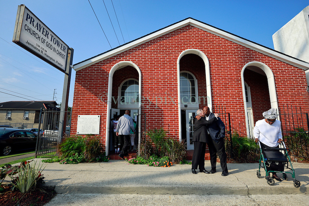 14 September 2013. Prayer Tower Church of God in Christ. New Orleans, Louisiana. <br /> Archbishop Gregory Aymond embraces Pastor Jermaine Hampton at the funeral for 11 yr old Arabian 'Ray Ray' Gayles, fatally shot September 2nd. Arabian was cradling a 1 yr old cousin whilst sat on the couch at home when gunmen pulled up outside and sprayed the house with bullets. Arabian was hit in the head and died shortly afterwards. NOPD is questioning 2 men in connection with the murder.<br /> Photo; Charlie Varley