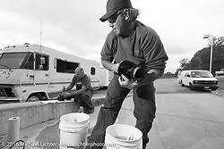 """After his HD VL suffered a catastrophic failure, Jason Sims worked with RJ on the cylinders on the Friday """"Rest Day"""" between stages 7 and 8 of the Motorcycle Cannonball Cross-Country Endurance Run in Junction City, KS., USA. Friday, September 12, 2014.  Photography ©2014 Michael Lichter."""