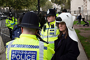 Extinction Rebellion climate change activist wearing a polar bear head is detained and spoken to by police as sites around Westminster are blocked on 8th October 2019 in London, England, United Kingdom. Extinction Rebellion is a climate group started in 2018 and has gained a huge following of people committed to peaceful protests. These protests are highlighting that the government is not doing enough to avoid catastrophic climate change and to demand the government take radical action to save the planet.