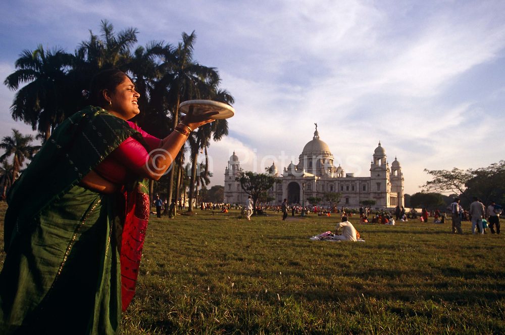 On a hot afternoon on Calcutta's Maidan, an Indian lady catches a frisbee disc in both hands in front of the glorious Victoria Memorial, the beautiful marble structure built by the British still during the days of the colonial Indian Raj. The lady is lit with golden light and her bottle green sari stands out from a background tree. She grimaces as she stretches to hold on to the frisbee and there are many hundreds of families and groups in the background, nearer to the white, domed building. Built between 1906 and 1921, it is a majestic white marble building at the southern end of the Maidan, a large expansive park in central Calcutta city. Nowadays it is a museum and group activities are being discouraged due to the fears that pollution will damage this fine structure that honours Queen Victoria, then Empress of India.