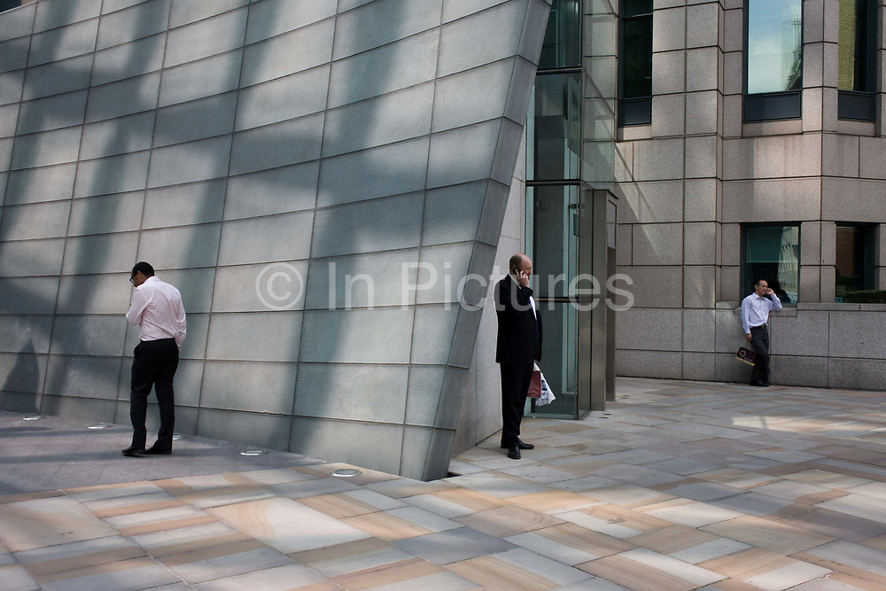 City workers make personal calls at the corner of a pedestrian pavement at Broadgate in the City of London.<br /> Three males spend quiet moment in the privacy of their own corner, beneath 1980s architecture. Broadgate Estate is a large, 32 acre (129,000 m²) office and retail estate in the City of London, owned by British Land and managed by Broadgate Estates. It was originally built by Rosehaugh and was the largest office development in London until the arrival of Canary Wharf in the early 1990s. The City is a major business and financial centre. Throughout the 19th century, the City was perhaps the world's primary business centre, and it continues to be a major meeting point for businesses