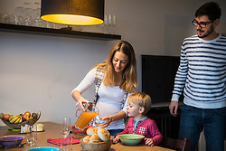 Mother pouring juice into a glass while son is watching, Munich, Germany