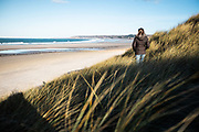 Woman walking through the sand dunes in low wintry sunlight at St Ouen's Bay, Jersey, Channel islands