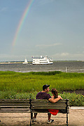A couple together in Waterfront Park with a rainbow Charleston, SC.