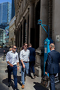 Businessmen walk past one of the few remaining police signal boxes on Threadneedle Street in the City of London, the capitals historic financial district, on 2nd August 2018, in London, England. The Police box is a public telephone kiosk or callbox for the use of members of the police, or for members of the public to contact the police. It was introduced in the United States in 1877 and was used in the United Kingdom throughout the 20th century from the early 1920s.