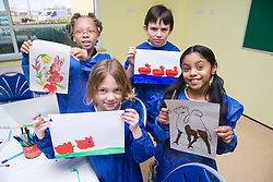 Group of children showing off the pictures they have made during a craft activity at their local leisure centre,