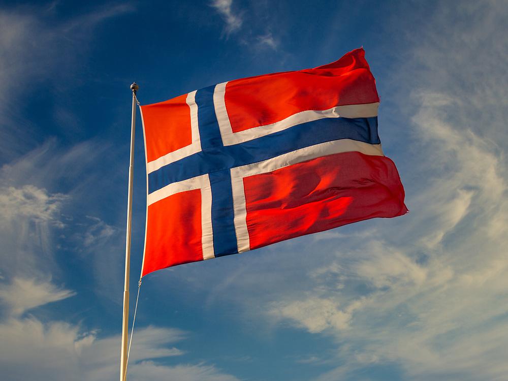 Solen skinner på norsk flagg som friskt blafrer i vinden, mot blå himmel med skyer.
