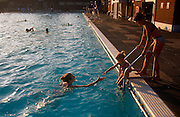 A mother reaches out to encourage her child to enter the warm, inviting waters of the Herne Hill Lido in south London, England