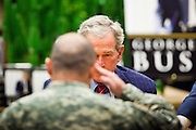 "09 DECEMBER 2010 - PHOENIX, AZ: Former President GEORGE W. BUSH salutes an American soldier and signs copies of his book, ""Decision Points"" at the Barnes & Noble Bookstore in Phoenix, AZ, Thursday, Dec. 9. More than 2,000 people lined up starting at 5AM to get copies of the former President's book, ""Decision Points."" A handful of protesters demonstrated against President Bush near the bookstore, calling him a ""war criminal.""  PHOTO BY JACK KURTZ"