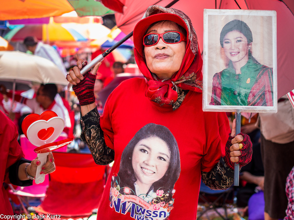 10 MAY 2014 - BANGKOK, THAILAND: A supporter of Yingluck Shinawatra, carrying a photo of Yingluck and wearing a tee shirt with Yingluck's picture on it at a Red Shirt rally in Bangkok. Thousands of Thai Red Shirts, members of the United Front for Democracy Against Dictatorship (UDD), members of the ruling Pheu Thai party and supporters of the government of ousted Prime Minister Yingluck Shinawatra are rallying on Aksa Road in the Bangkok suburbs. The government was ousted by a court ruling earlier in the week that deposed Yingluck because the judges said she acted unconstitutionally in a personnel matter early in her administration. Thailand now has no functioning government. Red Shirt leaders said at the rally Saturday that any attempt to impose an unelected government on Thailand could spark a civil war. This is the third consecutive popularly elected UDD supported government ousted by the courts in less than 10 years.    PHOTO BY JACK KURTZ
