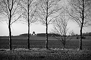 Somme WW1 Battlefield, July 1st-November 1916, France. Thiepval Memorial from the Albert-Bapaume Road. February 2014<br /> The Thiepval Memorial to the Missing of the Somme is a major war memorial to 72,191 missing British and South African men who died in the Battles of the Somme of the First World War between 1915 and 1918 with no known grave. It is near the village of Thiepval, Picardy in France.<br /> Designed by Sir Edwin Lutyens, the memorial was built between 1928 and 1932 and is the largest British battle memorial in the world. It was inaugurated by the Prince of Wales (later King Edward VIII) in the presence of Albert Lebrun, President of France, on 1 August 1932. The unveiling ceremony was attended by Lutyens.<br /> <br /> The memorial, which dominates the rural scene surrounding it, has 16 brick piers, faced with Portland stone. It was originally built using French bricks from Lille, but was refaced in 1973 with Accrington brick. The main arch is aligned east to west. The memorial's height is 140 feet (43 m) above the level of its podium, which to the west is itself 20 feet (6.1 m) feet above the level of the adjoining cemetery. It has foundations 19 feet (5.8 m) thick, required due to extensive wartime tunnelling beneath the structure.<br /> <br /> It is a complex form of memorial arch, comprising interlocking arches of four different sizes. Each side of the main arch is pierced by a smaller arch, oriented at a right angle to the main arch. Each side of each of these smaller arches is then pierced by a still smaller arch, and so on. The keystone of each smaller arch is at the level of the spring of the larger arch that it pierces; each of these levels is marked by a stone cornice. This design results in 16 piers, having 64 stone-panelled sides. Only 48 of these are inscribed, as the panels around the outside of the memorial are blank.<br /> <br /> The main arch is surmounted by a tower. In the central space of the memorial a Stone of Remembrance rests on