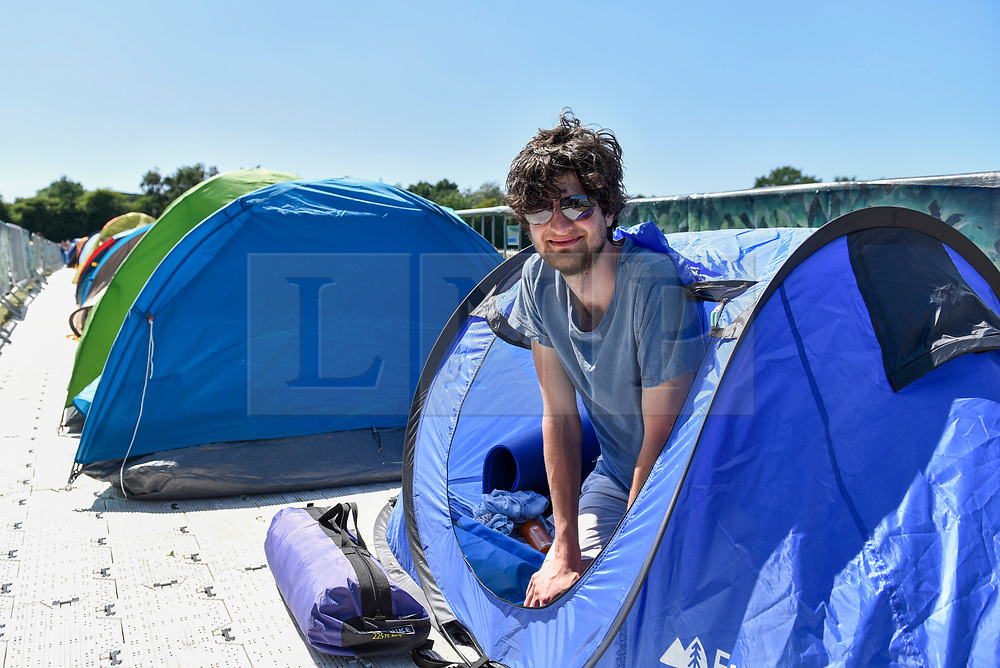 """© Licensed to London News Pictures. 30/06/2018. LONDON, UK.  Darius Platt-Vowles from Gloucestershire poses in his tent in Wimbledon Park.  He is the first in """"The Queue"""" for premium tickets, having arrived on Thursday 28 June, four days before the Wimbledon tennis championships are to begin on 2 July.  He hopes to be able to obtain tickets to centre court to see his idol, Roger Federer.  Photo credit: Stephen Chung/LNP"""
