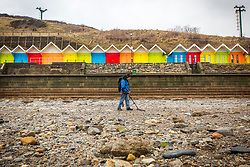 © Licensed to London News Pictures. 06/03/2018. Scarborough UK. Large parts of the beach in the North Bay of Scarborough have been left with no sand after storm Emma which has drawn metal detectors to hunt for treasure. Photo credit: Andrew McCaren/LNP