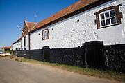 Whitewashed boathouse at the coastal village of Burnham Overy Staithe, north Norfolk coast, England