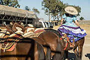 Saray Franco with the legendary Franco family of Charro champions, mounts her horse sidesaddle wearing the traditional Adelita costume during a Mexican rodeo practice session in the Jalisco Highlands town of Capilla de Guadalupe, Mexico. Women participants in the traditional Charreada are called Escaramuza and perform precision equestrian displays riding sidesaddle and garbed in Adelita dress.