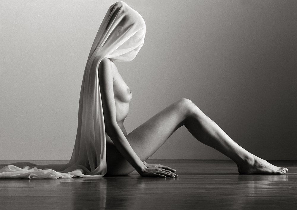 Black and white profile photo of nude woman sitting on wood floor with sheer pink cloth covering face