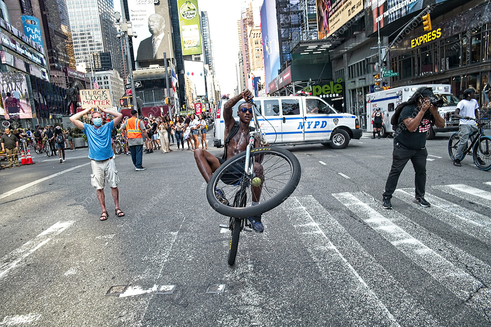NEW YORK, NEW YORK:  At least 200  young boys and girls ride their bikes by a Black Lives Matter rally for Breonna Taylor at Times Square in New York, New York on Sunday, August 9, 2020. New York City community organizers are marking a week of action in remembrance of Taylor.  It was 150 days to the day the Taylor was killed by Louisville, KY cops on a false warrant and with no arrests made to date. (©Brian Branch-Price/TheFotodesk)