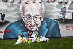© Licensed to London News Pictures. 03/02/2021. Tamworth, Staffordshire, UK. Tom Flowers . Flowers in the memory of Sir Tom Moore have been laid under a mural painted in Tamworth Road, Tamworth earlier today. Photo credit: Dave Warren / LNP